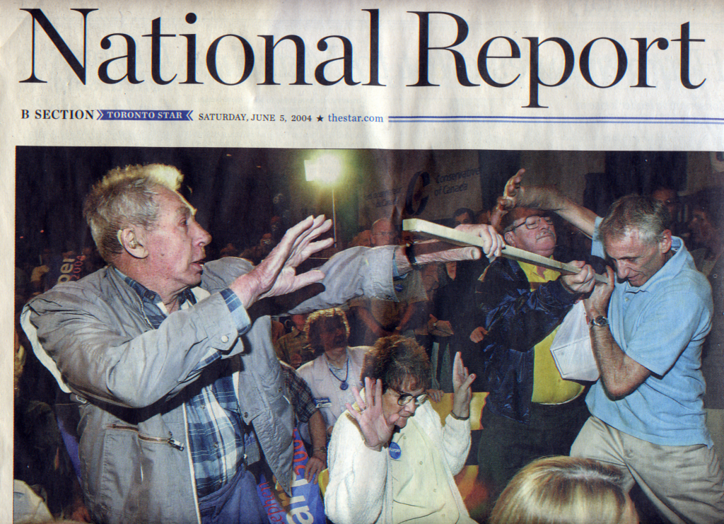 Man getting hit by a stick at a Conservative Party of Canada rally for Stephen Harper in 2004.