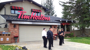 House with Tim Hortons sign on garage roof.