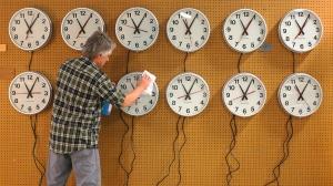 photo of man changing clocks