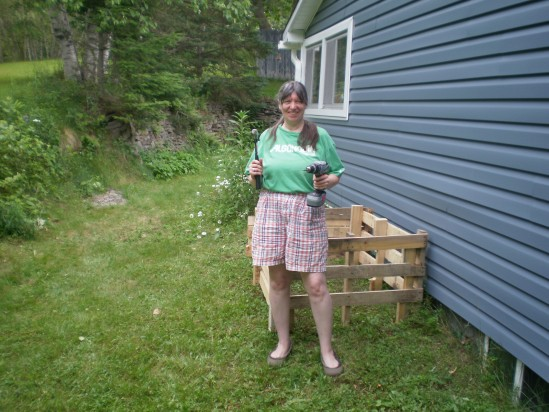 Woman posing with hammer and cordless power screwdiver near a project she just saw completed.