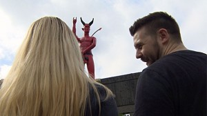 A couple looking at a statue of a devil, blocking the camera's view of the devil's private parts.
